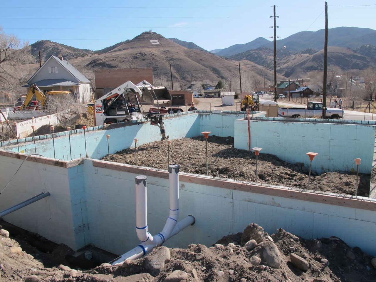 """Pouring """"dirty"""" roadbase--the kind with lots of fines so it compacts well--under what will be the slab floor of my tiny house. (Not the sewer pipe going through the foundation in the foreground and the orange water pipe in the background where the kitchen will be.)"""