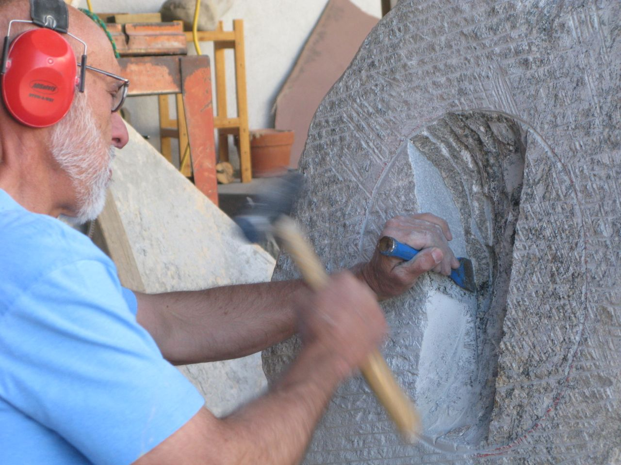 Richard chisels the excess from a one-ton granite boulder.