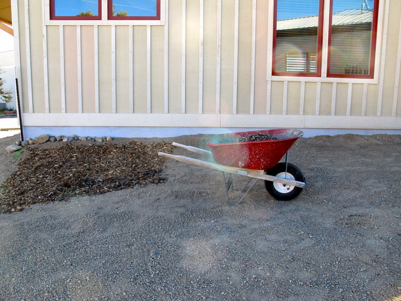 Spreading mulch over the seeds. (The large windows are my office.)