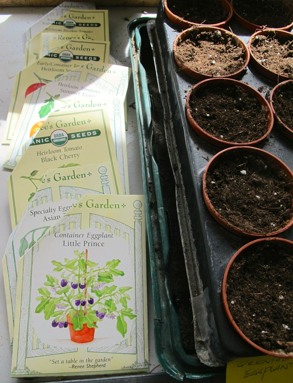 Seed packets and seedling pots, filled with organic potting soil.