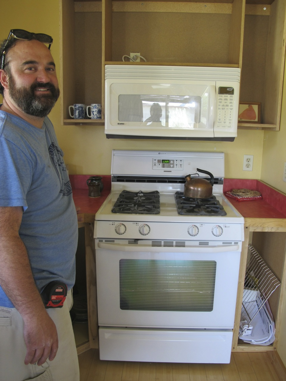 Andrew with the cabinet he installed over the stove in the guest cottage at Terraphilia