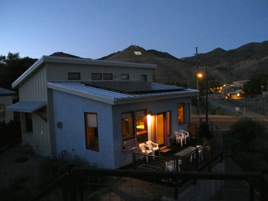 Creek House, my small house, on a clear evening. Those reflective dark panels on the roof are a 3.0 kw photovoltaic array.