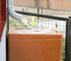 Rain barrel overflows at the height of the storm.