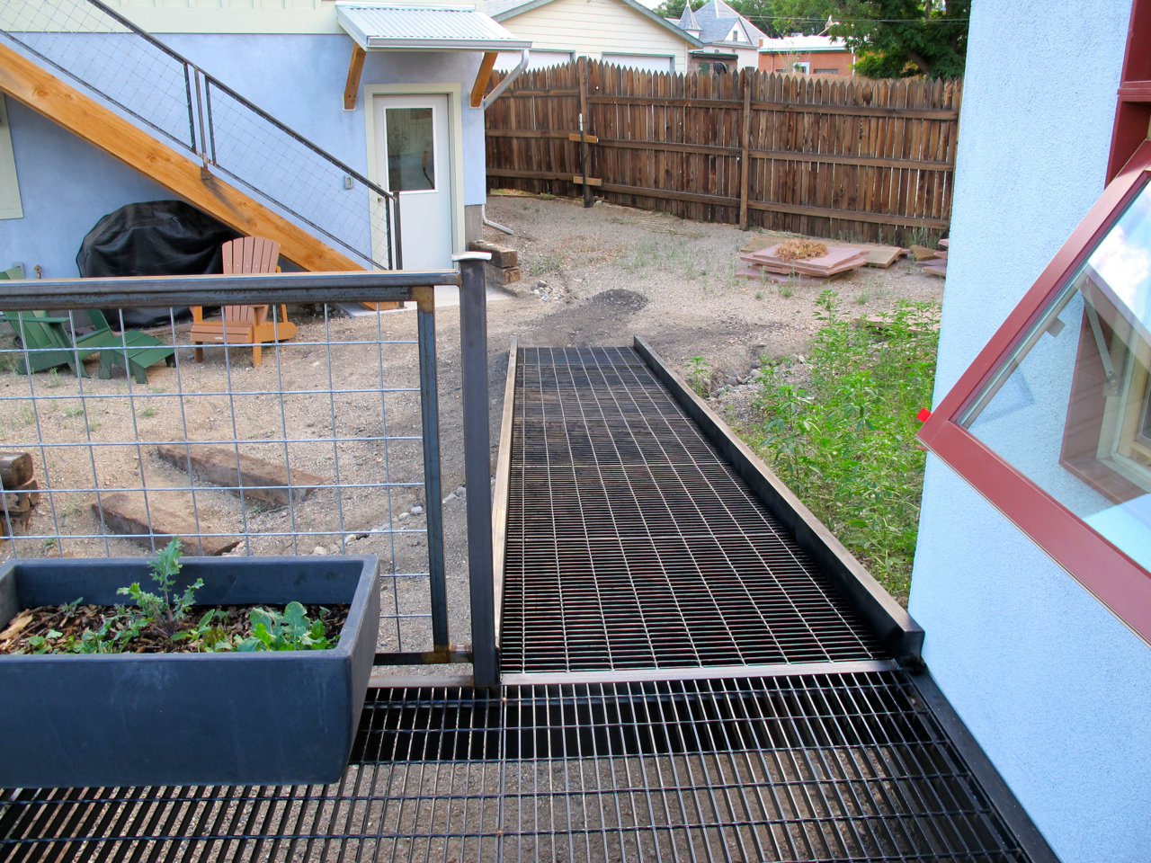 Steel grate ramp leading from the front deck to the side garage door.