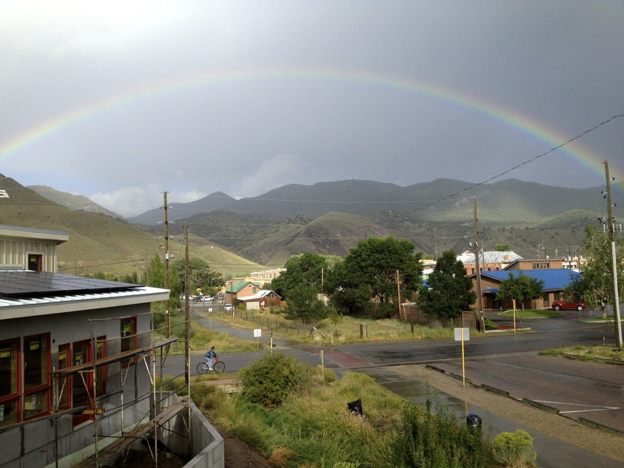 A rainbow stretches over Salida and the Arkansas Hills at sunset after a late-summer shower.