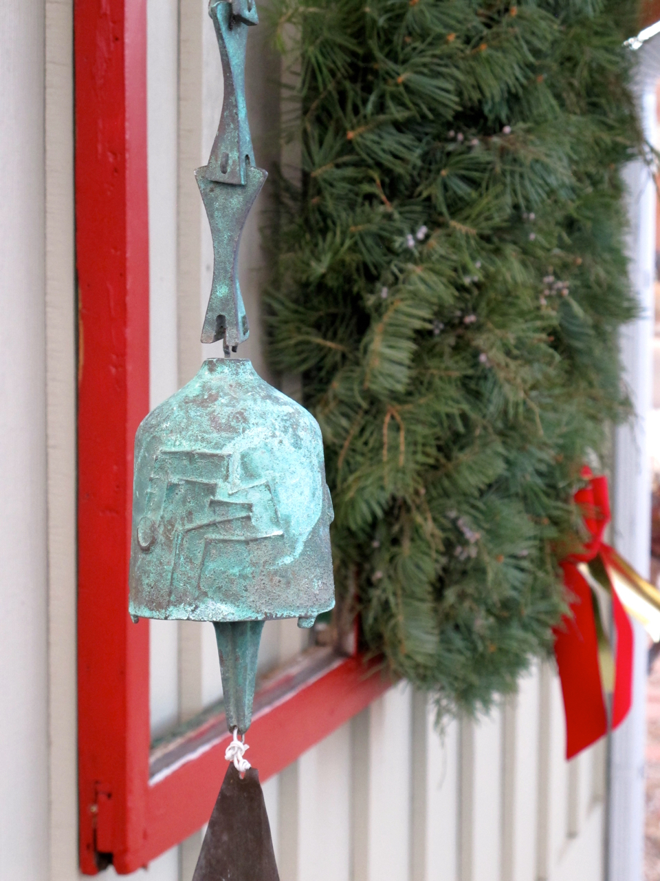 A bronze temple bell I hung near the wreath on Creek House where I hear the wind in the bell's deep voice.