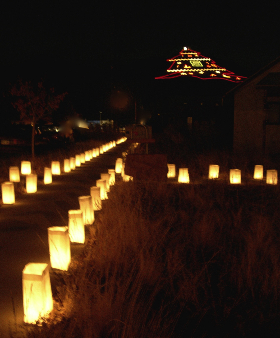 The luminarias lining the block at Terraphilia with Christmas Mountain in the background.